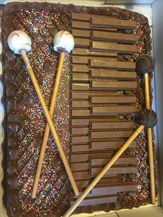 Marimba cake! Used a store bought cake.  Used KitKat bars for marimba bars and used cake pops for mallets.