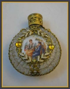 """This vintage Czech mini perfume bottle measures just 2 1/8"""" tall. On the front of the bottle is a courting scene, with a man playing music for his lady fair. The bottle has a band of filigree completely encircling it with mounted Citron Yellow colored rhinestones on the shoulders. The same Citron Yellow stones are mounted on the filigree on each side of the courting scene. The top of the stopper has a portrait of a dark haired maiden."""