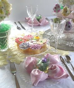 The napkin fold is called Lotus, yellow glass flowerpot candleholders filled with Easter grass and foil wrapped candy to top off each plate for the finishing touch