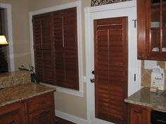 English Chestnut stained plantation shutters provide a nice contrast to white trim and warms up the kitchen. The color of the shutters also complements the stained kitchen cabinetry. Decor, Kitchen Cabinetry, Southern Accents, Remodel, Tall Cabinet Storage, Home Decor, White Trim, Renovations, Shutters