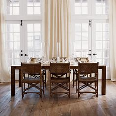 More neutral beachside chic in this dining room with lots of tall windows, a weathered wood floor, and long gauze drapes