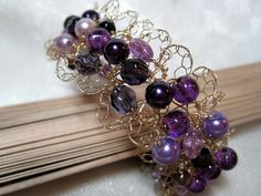 """(The outside wire work is chain stitch slipstitched at intervals.)  The Lacy Purple Bead Bracelet is a piece of crocheted wire beaded jewelry I made using very fine (thin) gold wire and a variety of purple glass beads.   I used purple crackle glass beads in rice shape and round, glass pearls, and some faceted glass beads, including ones with a purple metallic finish.  This bracelet is 7.5"""" long and about 1"""" wide, and fastens with a simple gold toggle clasp."""