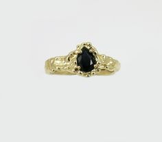 """A starless black teardrop sapphire set into a textured band of 14k yellow gold.Traditionally Sapphires symbolize sincerity and faithfulness. Before Diamonds gained popularity in the 20th century colored stones like Rubies, Emeralds and Sapphires were the favored stone for engagement rings. This ring would make for a special modern engagement ring with a romantic nod to the past.Due to the nature of the process no two rings are alike. Unless your size is marked """"ready to..."""
