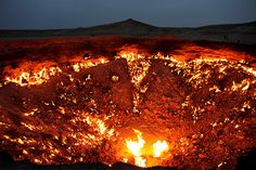 """The Door To Hell: The Derweze area is rich in natural gas. While drilling in 1971, Soviet geologists tapped into a cavern filled with natural gas. The ground beneath the drilling rig collapsed, leaving a large hole with a diameter of 70 metres (230 ft). To avoid poisonous gas discharge, it was decided to burn it off. Geologists had hoped the fire would use all the fuel in a matter of days, but the gas is still burning today. Locals have dubbed the cavern """"The Door to Hell""""."""