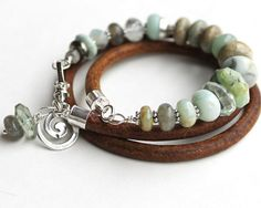 Gemstone and leather wrap bracelet. Leather bracelet with Jade, blue Peruvian opal, Brazilian aquamarine, Amazonite, Aqua terra jasper, aventurine and on 5mm natural leather cord. Features a labrodorite and green amethyst drop thought to increase harmony and inspiration, confidence and grace. Sterling silver accent beads, Solid silver Spiral and findings and closed with a heavy sterling locking clasp. 21 1/2 inch length Circles the wrist 4 times. Fits up to 7 inch wrist