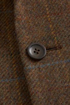 Detailed shot of the James Aubrey brown tweed sports jacket.
