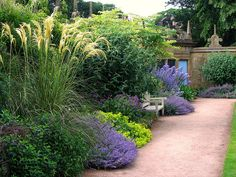 [A Summer Garden Scene from Hardwick Hall in Derbyshire].  Plants spilling out over the garden boarders!