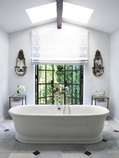 Elegant bathroom with light gray walls and freestanding stone bathtub. Carrara marble floor tiles with black diamond accent. Black iron and glass patio doors leading to balcony, flanked by antique mirrored wall sconces and glass and iron accent tables.