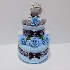 2 Tier Zebra Themed Boys Blue Nappy Cake.  Our 2 tier Zebra Themed Boys Blue Nappy Cake includes the following:  2 Tiers of Premium Branded Size 3 Nappies (4-9kgs/9-20lbs) 1 Soft High Quality Fleece Blanket 1 Quality Muslin Square 1 Plush Zebra Soft Toy 1 Bodysuit 1 Pair Scratch Mitts 1 Pair Socks 1 Bib 1 re-useable Cake Board  Available at www.cheshirenappycakes.co.uk