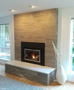 Really like the big tiles, but the texture look of stone. Also love the black and metal frame to make the center pop. Don't like the hearth. Would like mantle made of same material instead.