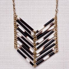 This chevron-style necklace is made out of a brass chain and real porcupine…
