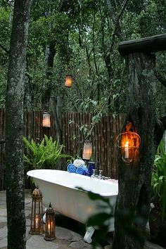 Glass lanterns around an outdoor bathtub.