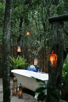 Glass lanterns around an outdoor bathtub.