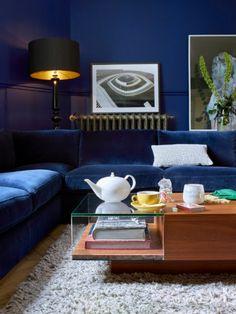 Un canapé en velours bleu marine. Dotée d'une assise moelleuse, il est ton sur ton avec le mur du salon, créant ainsi une atmosphère mystérieuse et élégante. L'idée à retenir : Le canapé d'angle devant la fenêtre, pour profiter de la lumière du jour. Mise en scène Habitat