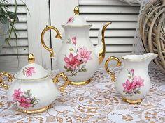 1 Moccakanne, 1 Zuckerdose, 1 Milchkännchen aus weißem Porzellan, mit üppigem Golddekor, Chippendale Form, mit rosa Blumen beidseitig romantisch verziert.