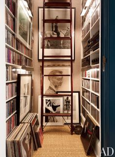 Library with black and white artwork, white bookshelves, brown carpet, and wood ladder
