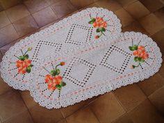 Dois tapetes de crochê com flores aplicadas, medindo 110 x 43 cm.    Confeccionado com barbante cru e barbante multicolorido laranja e verde.    Pode ser feito sob encomenda nas cores de sua preferência, consulte mostruário de cores. R$ 158,00