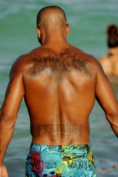 CARPE DIEM - Shemar Moore shows off a new tattoo as he frolics in the ocean with his girlfriend and a female friend in Miami