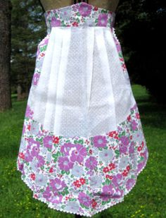 Vintage apron of white dotted swiss with floral pockets and hem, white rickrack.trim.. Excellent condition. Click image for close up.  AP920 - $33  ... http://www.rickrack.com/vintage-aprons-3.html