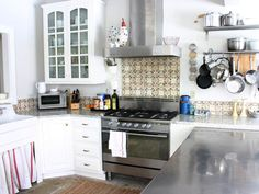 Love the European feel to this kitchen with the tumbled stone floors and rustic terra cotta backsplash tiles.