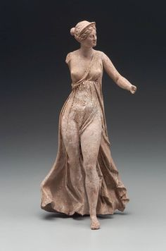 Flying Nike (Victory). Greek, East Greek, Hellenistic Period, 2nd century B.C. Statuette of flying Nike (Victory). She is looking to the right. She has her left arm extended. She is wearing a transparent high-belted, sleeveless chiton, which leaves her right breast and left leg uncovered. She has her hair in flat waves ,with a ribbed crown (stephane).