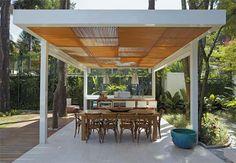 Pergolado com estrutura metálica e cobertura de madeira.