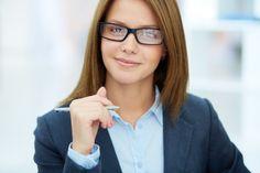 Primer plano de ejecutiva con gafas sujetando un bolígrafo Foto Gratis