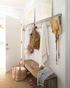 The back hall of this Ohio lake home was turned into a mudroom outfitted with salvaged door frames (with rope balls for hooks) and a bench crafted from reclaimed barn wood.   - CountryLiving.com