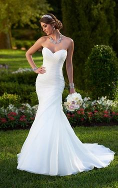 Sweetheart neckline strapless fit-and-flare wedding gown featuring an asymmetrical ruched bodice and skirt with a full skirt just below the hip.