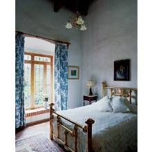 A pretty guest room with toile curtains awaits a visit by one of the couple's many grandchildren.
