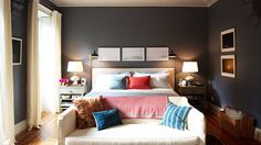 Dark walls in the bedroom with red and blue pillows on neutral bed