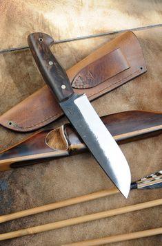 COUTEAU 302C75 et vieux noyer pour ce couteau de 29cm. La lame offre un tranchant légèrement recurve de 16 cm. - Fred M La poignée de presque 13 cm est constituée d'un ensemble de cuir, vieux noyer et rivets en laiton dont un mosaïqu
