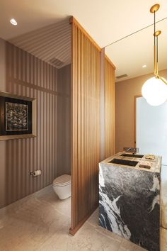 In this modern powder room, a wood slat wall separates the vanity area from the toilet, without blocking the light from the pendant light. #WoodSlatWall #PowderRoom #ModernBathroom