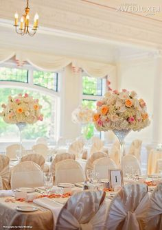 Beautiful white reception with white and orange flowers.