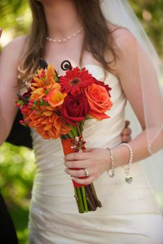 Fall bridal bouquet in reds, tangerines and coral hues.  Flowers: Visual Impact Design  Photo: Sharpe Weddings  Venue: Newcastle Wedding Gardens