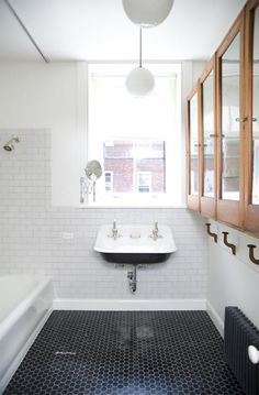 the black penny tile, vintage trough sink. subway tile with dark grout! I want to incorporate all of these in the boys bath. A Brownstone in Brooklyn by Elizabeth Roberts: Remodelista - Model Home Interior Design Old Bathrooms, Small Bathroom, Bathroom Black, Modern Bathroom, White Bathrooms, Penny Tile Bathrooms, Bathroom Interior, Master Bathroom, 1920s Bathroom