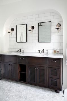 A beautiful arch shape frames the white tile wall above this double vanity. Dark wooden cabinetry is a beautiful contrast to the white and gray marble flooring, white countertops and white walls. Three glass-globed light fixtures are mounted between the matching mirrors to fully light the arched area.
