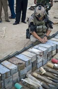 SOF Operator reviewing confiscated weapons cache.