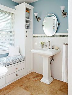 The lithe lines of the pedestal sinks make the bathroom airy and spacious, while the storage units flanking the window are perfect for linens and bathroom necessities. Open shelving provides display space for the homeowner's collection of vintage containers.