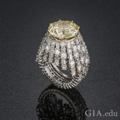 Natural 11.49 carat fancy light yellow diamond ring accented by round brilliant cut diamonds and baguettes.