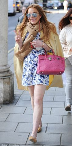 Peace and love: Lindsay Lohan flashed her trademark pose as she strolled along the streets...