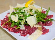 Beef Carpaccio: Thinly Sliced Beef Tenderloin Served Raw Under Arugula Salad with Mustard Vinaigrette
