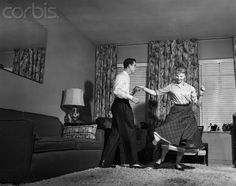 1950s Teen Couple Doing Jitterbug Rock And Roll Dance In Living Room Man Woman Boy Girl