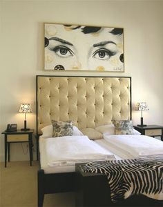 See the 2 comforters on the bed, that is typical for German beds. Bed in Berlin :) Love that art piece above the headboard  !