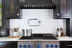 Instead of an expensive tile backsplash, this family of enthusiastic cooks chose a pot filler that stands in as a focal point above the stove.