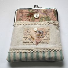 Gorgeous Clutch Purse.Made with pretty cottons and linen mix.  Featuring a fabric collage on the front and finished with lace and vintage buttons.Size 16cm x 15cm.This purse is handmade and is one of a kind.It is the perfect size to hol...