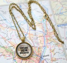 This 24 inch chain necklace features a 1 inch pendant with the Mark Twain Quote Explore Dream Discover printed on a high quality map image and sealed