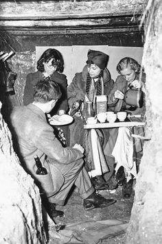 This is typical of the way Londoners had breakfast in England, Sept. 6, 1939, after the air raid warning had sounded. Breakfast was in the family dugout--this one in a garden?with a gasmask hanging ready. (AP Photo)