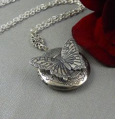 This steam punk inspired silver locket is 28 long. Antique sterling silver plated locket with floral patterns on the sides, is embellished with unique designed and rich texture steampunk antique silver butterfly embellishment. Pendant is hanging from antique finished silver floral