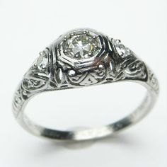 Filigree Darling: Petite but powerful, with more elegant swirling detail then one usually finds in a ring of this scale complete with a very bright white center diamond. Ca.1915.  Maloys.com